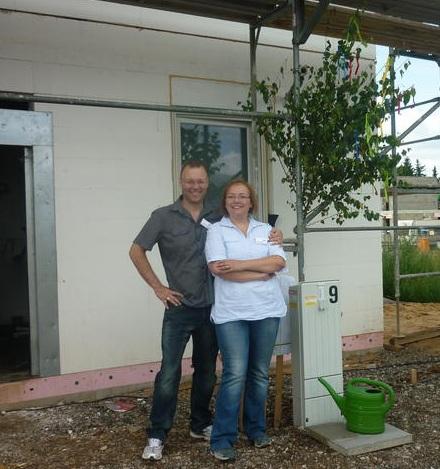 Die Bauherren mit Rohbaubäumchen vor dem Haus
